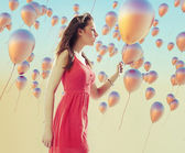 Young brunette woman among the balloons — Stock Photo