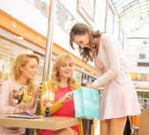Attractive lady showing her girlfriends some shopping — Stock Photo