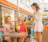 Laughing female friends in the shopping mall cafe — Stock Photo