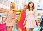 Happy girlfriends in the shopping mall — Stock Photo