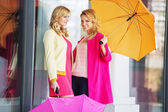 Attractive girlfreinds carrying the umbrellas — Foto de Stock