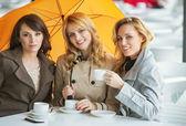Three women, the coffee and the umbrella — Stock Photo