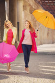 Two attractive girlfreinds with the umbrellas — Стоковое фото
