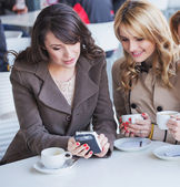 Cheerful women playing the mobile phone — Stockfoto