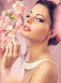 Brunette beautie with the flowers — Stock Photo