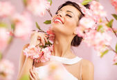 Pleased brunette woman among the flowers — ストック写真