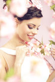 Glad brunette lady with the flowers in hair — Stock Photo
