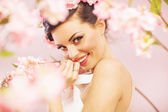 Glad smiling woman with flowers in hair — Stock Photo
