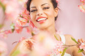 Pretty brunette lady among the flowers — Stock Photo