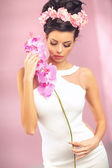 Sensual brunette girl with flower — Stock Photo