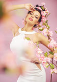 Beautiful smiling woman with spring flowers — Stock Photo