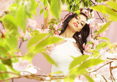 Brunette lady among the greenery and pink flowers — Stok fotoğraf