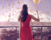 Young woman staring at thousands of the balloons — Stock Photo