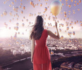 Young lady and the city of the balloons — Stock Photo