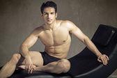 Elegant muscular guy in fashion pose — Stock Photo