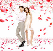 Elegant young couple in the petal rain — Stock Photo