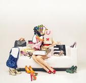Garota atraente com pilha de sapatos — Fotografia Stock