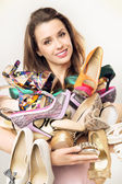 Portrait of the woman with plenty of shoes — Stock Photo