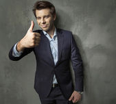 Man in suit showing the OK gesture — Stock Photo