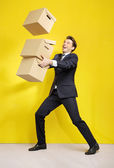 Cheerful businessman with paper boxes — Stock Photo