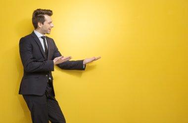 Handsome brunette businessman indicates something