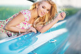 Attractive blonde girl riding the blue cadillac — Stock Photo