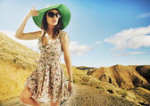 Brunette cutie with huge sunglasses and green hat — Stock Photo