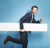Elegant young man running with the board — Stock Photo