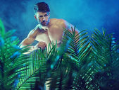 Attractive muscular man in the jungle — Stock Photo