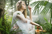 Sensual young lady among the greenery — Stock Photo