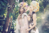Two forest nymphs weraing fancy hats — Stock fotografie