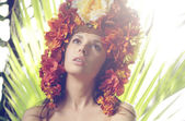 Pretty lady wearing hat made of flowers — Stock Photo