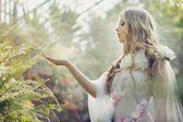 Blonde cutie touching the leaves of fern — Stock Photo