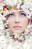 Pretty female face among the petals — Stock Photo