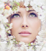 Charming girl's face among petals — Stock Photo