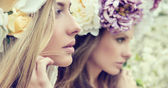 Portrait of the two gorgeous ladies with flowers — Stock Photo