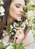 Attractive woman smelling wild flowers — Stock Photo