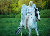 Bare feet angel riding a horse — Stock Photo
