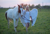 Sensual angel walking with the horse — Stock Photo