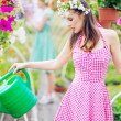 Gorgeous brunette watering the flowers — Stock Photo
