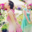 Two sexy ladies smelling the flowers — Stock Photo