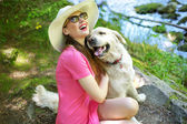 Attractive woman playing with lovely dog — Stock Photo