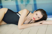 Attractive woman resting by the pool — Stock Photo