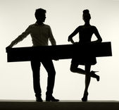 Elegant couple holding the empty board — Stock Photo