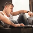 Smiling young man working on laptop at home — Stock Photo #5489632