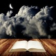 Open blak book on wooden table with night sk — Stock Photo