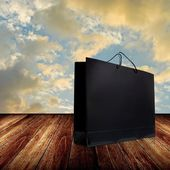 Torba na zakupy na drewnianym stole z rana niebo — Zdjęcie stockowe