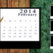 Calendar 2014 set with photo frame on wooden floor and grass background — Stock Photo
