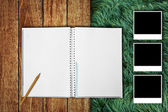Notebook with photo frames on wooden floor and grass field background — Stock Photo