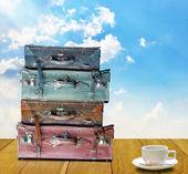 Listo para viajar en concepto de mañana, vieja bolsa de viaje y una taza de café en la mesa de madera — Foto de Stock